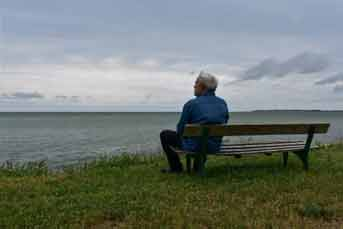 Man sitting on a bench looking out over water