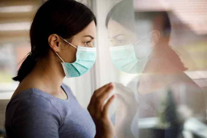 Woman wearing mask looking outside, forlorn